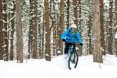 Ciclista no azul que monta o Mountain bike no inverno bonito Forest Extreme Sport e no conceito Biking de Enduro Imagem de Stock Royalty Free