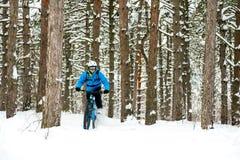 Ciclista no azul que monta o Mountain bike no inverno bonito Forest Extreme Sport e no conceito Biking de Enduro Fotografia de Stock