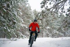 Ciclista no Mountain bike vermelho da equitação no inverno bonito Forest Extreme Sport e no conceito Biking de Enduro Fotografia de Stock