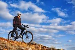 Ciclista no revestimento preto que monta o monte da bicicleta para baixo Conceito extremo do esporte Espaço para o texto Foto de Stock Royalty Free