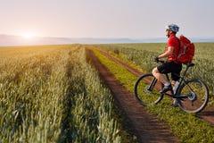 Ciclista novo com o ciclista da montanha no trajeto do campo no campo contra o nascer do sol Fotos de Stock Royalty Free