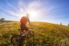 Ciclista novo com o ciclista da montanha no trajeto do campo no campo contra o nascer do sol Fotografia de Stock