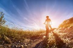 Ciclista novo com o ciclista da montanha no trajeto do campo no campo contra o nascer do sol Imagem de Stock
