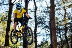Ciclista profesional en camiseta amarilla y casco que monta la bici de montaña en Forest Extreme Sport Concept Imágenes de archivo libres de regalías