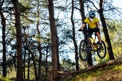Ciclista profesional en camiseta amarilla y casco que monta la bici de montaña en Forest Extreme Sport Concept Fotografía de archivo libre de regalías