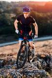 Ciclista profesional en casco azul y las gafas de sol anaranjadas que montan la bici en el top de la roca Concepto extremo del de Foto de archivo libre de regalías