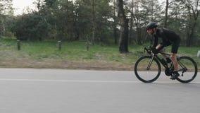 Ciclista profesional flaco apto que monta pedaling rápido y fuerte de la bicicleta de la silla de montar en el parque