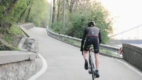 Ciclista profesional fuerte con los músculos fuertes de las perneras elásticas que montan cuesta arriba de la silla de montar Det almacen de video
