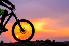 Ciclista profesional que descansa con abajo la bici de la colina en la roca en la puesta del sol Fotos de archivo