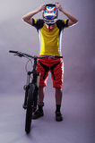Ciclista profesional que lleva un casco en un fondo gris Fotos de archivo