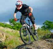 Ciclista profesional que monta la bici en rastro de montaña hermoso de la primavera Deportes extremos Fotografía de archivo