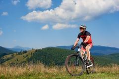 Ciclista profissional do desportista no sportswear e capacete que dá um ciclo uma bicicleta na grama alta imagem de stock
