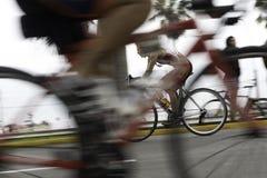 Ciclista que compite con en el camino Foto de archivo libre de regalías