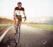 Ciclista que compite con en el camino en la puesta del sol Imagen de archivo libre de regalías