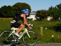 Ciclista que compite con en medio acontecimiento ironman. Imagen de archivo