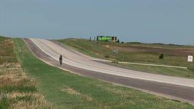Ciclista que conduce a lo largo del camino en el desierto almacen de video