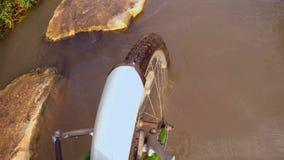 Ciclista que cruza una corriente fangosa con la bicicleta - cercana para arriba en la rueda delantera almacen de video