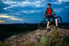 Ciclista que descansa con la bici de montaña en la roca en la puesta del sol Imagen de archivo libre de regalías