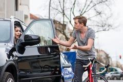 Ciclista que grita mientras que desvía para evitar la colisión en una calle muy transitada imagen de archivo libre de regalías