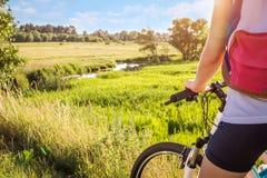 Ciclista que mira en el río abajo del campo Foto de archivo