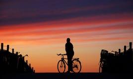 Ciclista que mira en la puesta del sol imagen de archivo libre de regalías