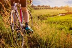 Ciclista que monta abajo del campo al río Foto de archivo