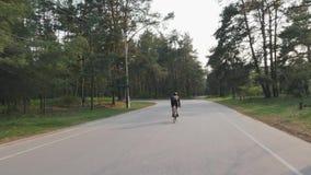 Ciclista que monta apenas no parque ao treinar para a raça Siga para trás o tiro da bicicleta pedaling da estrada do ciclista filme