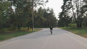 Ciclista que monta apenas no parque ao treinar para a ra?a Siga para tr?s o tiro da bicicleta pedaling da estrada do ciclista Mov vídeos de arquivo