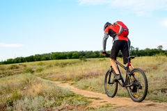 Ciclista que monta a bicicleta na fuga de montanha bonita da mola Imagem de Stock Royalty Free