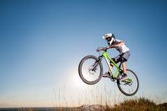 Ciclista que monta cuesta abajo en la bici de montaña en la colina Fotos de archivo libres de regalías