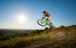 Ciclista que monta cuesta abajo en la bici de montaña en la colina Fotografía de archivo libre de regalías