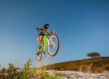 Ciclista que monta cuesta abajo en la bici de montaña en la colina Foto de archivo libre de regalías