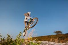 Ciclista que monta cuesta abajo en la bici de montaña en la colina Fotos de archivo