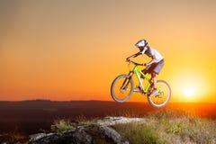 Ciclista que monta cuesta abajo en la bici de montaña en la colina Imágenes de archivo libres de regalías