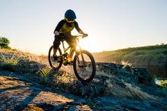 Ciclista que monta la bici de montaña en el verano Rocky Trail en la tarde Deporte extremo y concepto de ciclo de Enduro foto de archivo libre de regalías