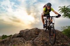 Ciclista que monta la bici en Autumn Rocky Trail en la puesta del sol Deporte extremo y concepto Biking de Enduro imagen de archivo