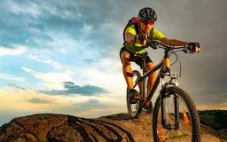 Ciclista que monta la bici en Rocky Trail en la puesta del sol Deporte extremo y concepto Biking de Enduro imagen de archivo