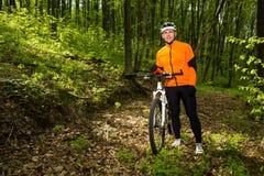 Ciclista que monta la bici en un rastro en bosque del verano Imagen de archivo libre de regalías