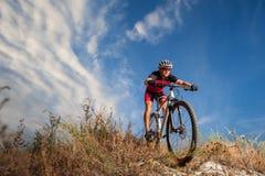 Ciclista que monta su bici abajo en rastro de montaña Fotos de archivo libres de regalías