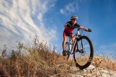 Ciclista que monta su bici abajo en rastro de montaña Foto de archivo