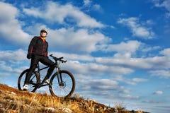 Ciclista que monta su bici abajo en rastro de montaña Cielo y nubes hermosos en fondo Foto de archivo