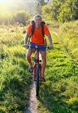 Ciclista que monta uma bicicleta na estrada Fotografia de Stock