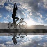 Ciclista que monta una bici del camino en la puesta del sol imágenes de archivo libres de regalías