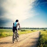 Ciclista que monta una bici en la carretera nacional imagenes de archivo