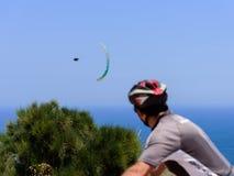 Ciclista que olha em voar paragliders em tandem no céu sobre opinião bonita unfocused 02 do mar, mar fotos de stock