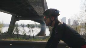 Ciclista seguro focalizado em uma bicicleta Sun brilha completamente Rio e ponte no fundo Feche acima da vista lateral Conceito d vídeos de arquivo