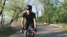 Ciclista sicuro messo a fuoco che pedaling dalla sella La parte anteriore segue il colpo Ciclista professionista che indossa attr video d archivio