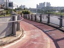 Ciclista sulla pista ciclabile vicino del fiume di Pinheiros fotografia stock