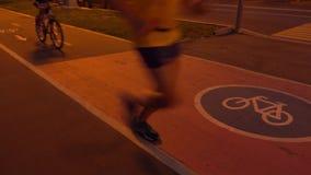 Ciclista y corredor que pasan cerca en la trayectoria urbana de la bici en la noche vídeo 4K almacen de video