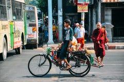 Ciclista y monje en las calles de Rangún Imagenes de archivo